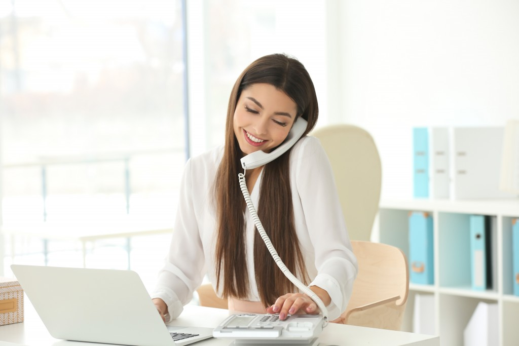 Woman talking by the telephone while working with laptop in office