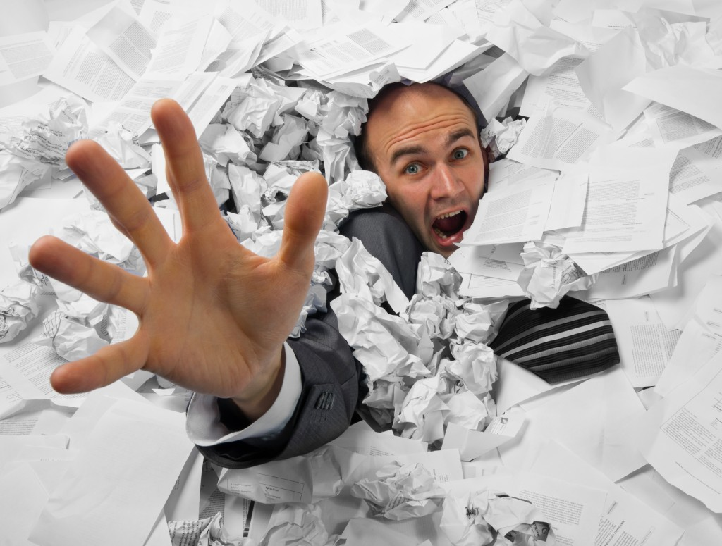 man drowning in paperwork