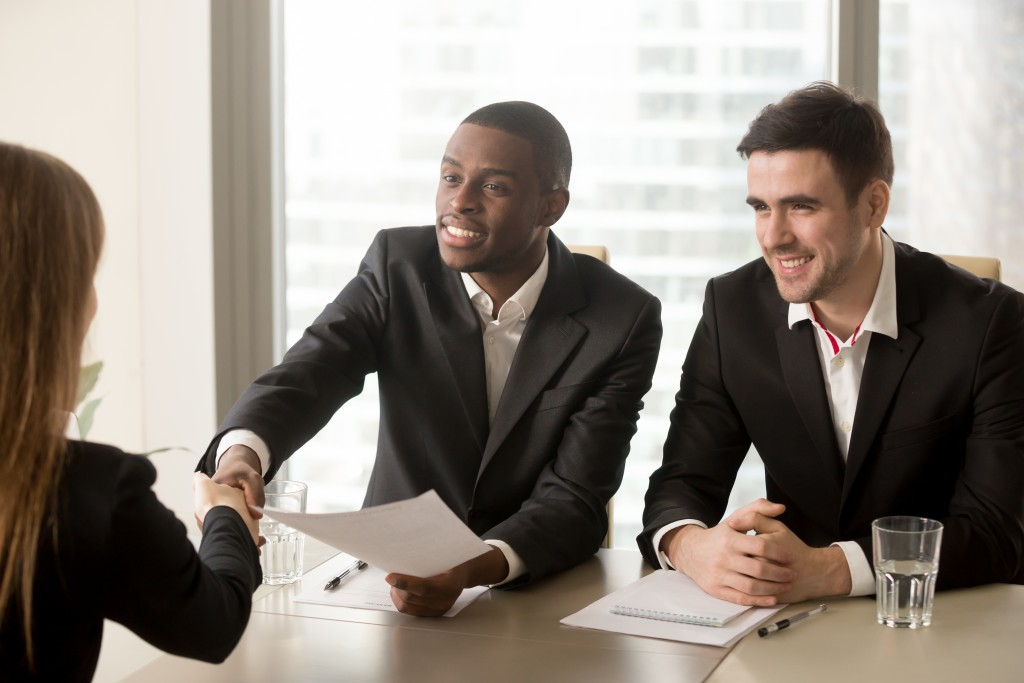 two men interviewing a girl
