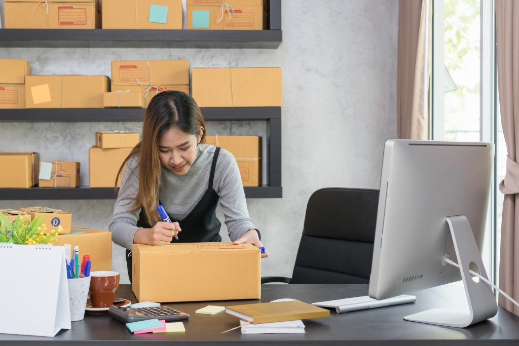 businesswoman writing on boxes