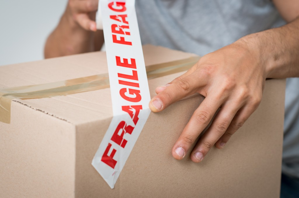 man marking a box with fragile sign