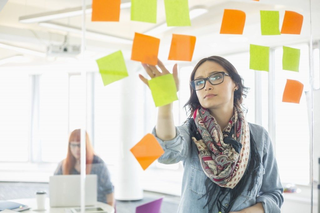 Creative businesswoman sticking sticky notes on glass