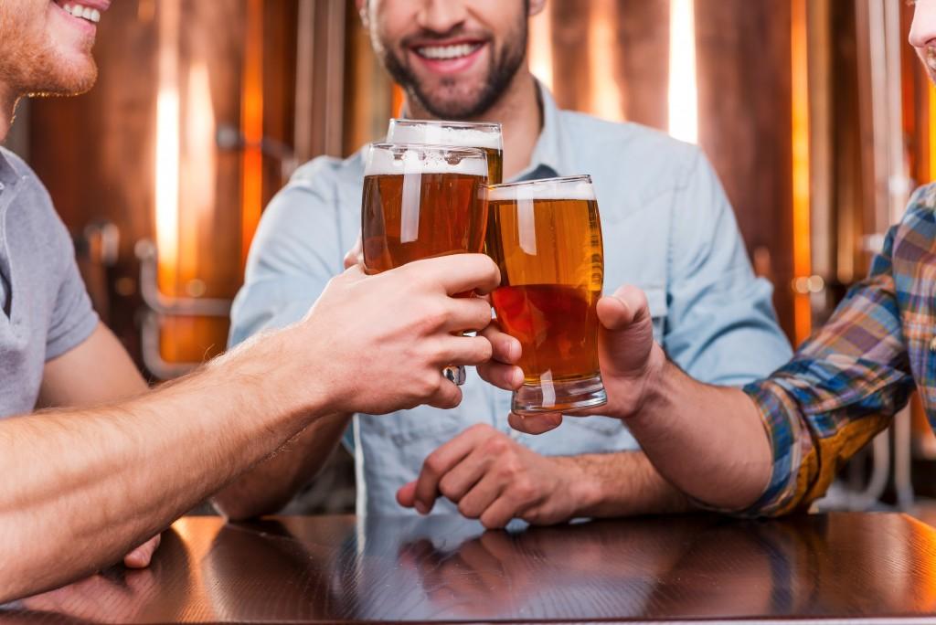 three men drinking beer