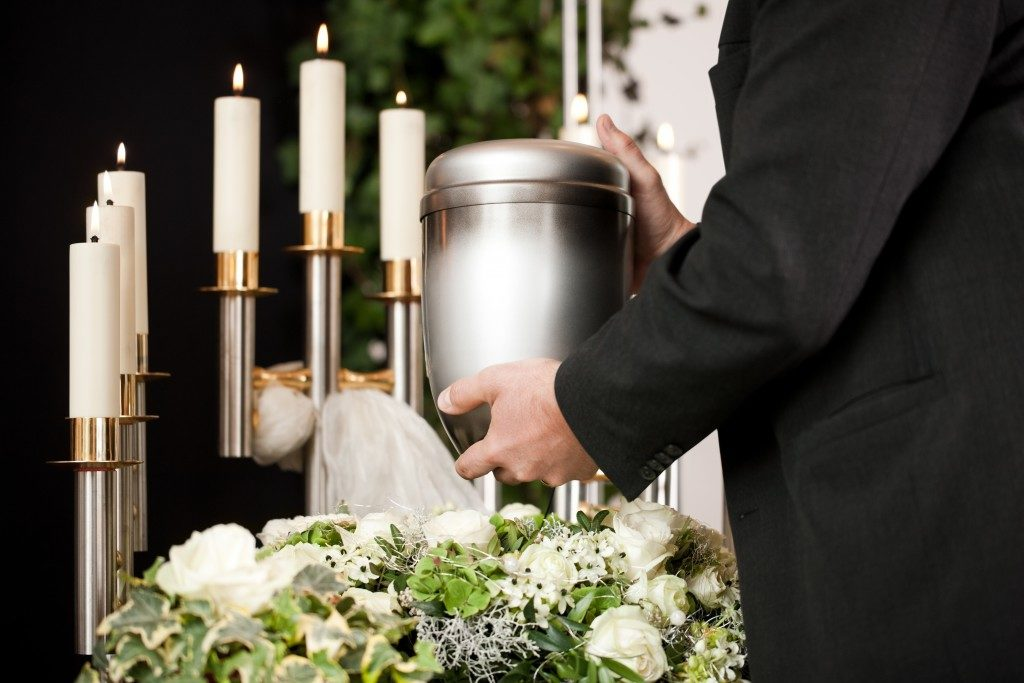 man holding an urn at a funeral