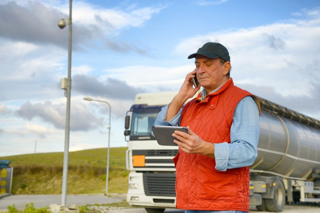 man on his phone while checking another device, having a commercial truck as a background