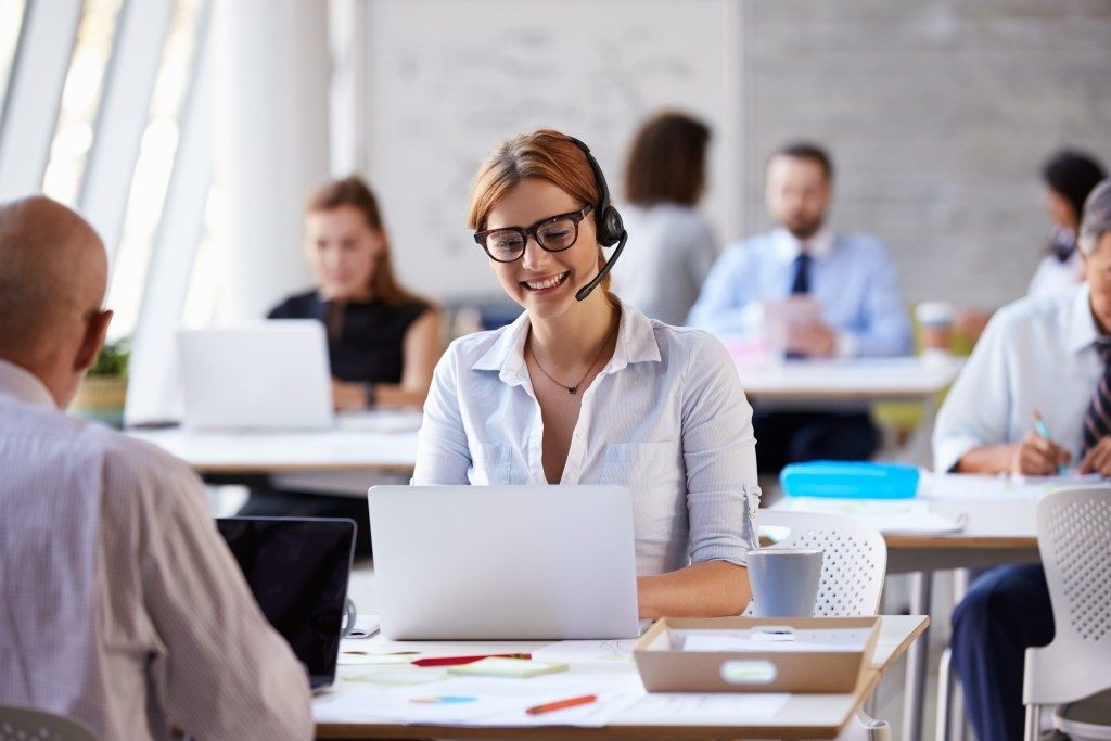woman wearing a headphone with speaker in an open office