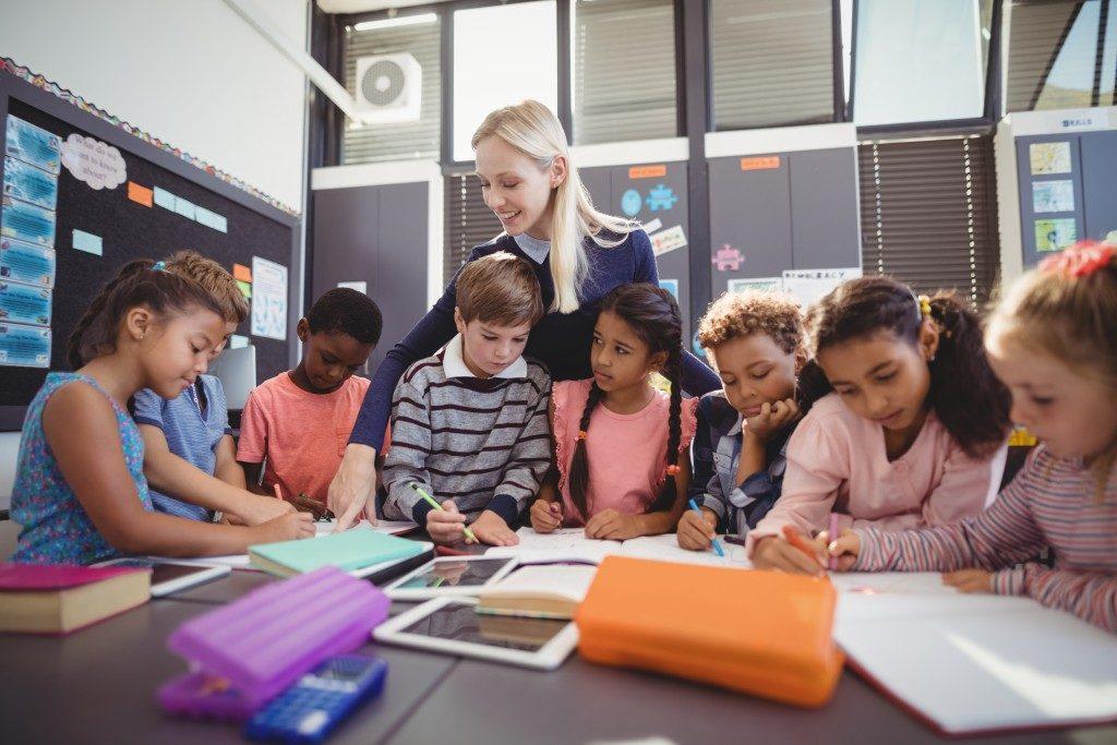 teacher guiding her students in their art class