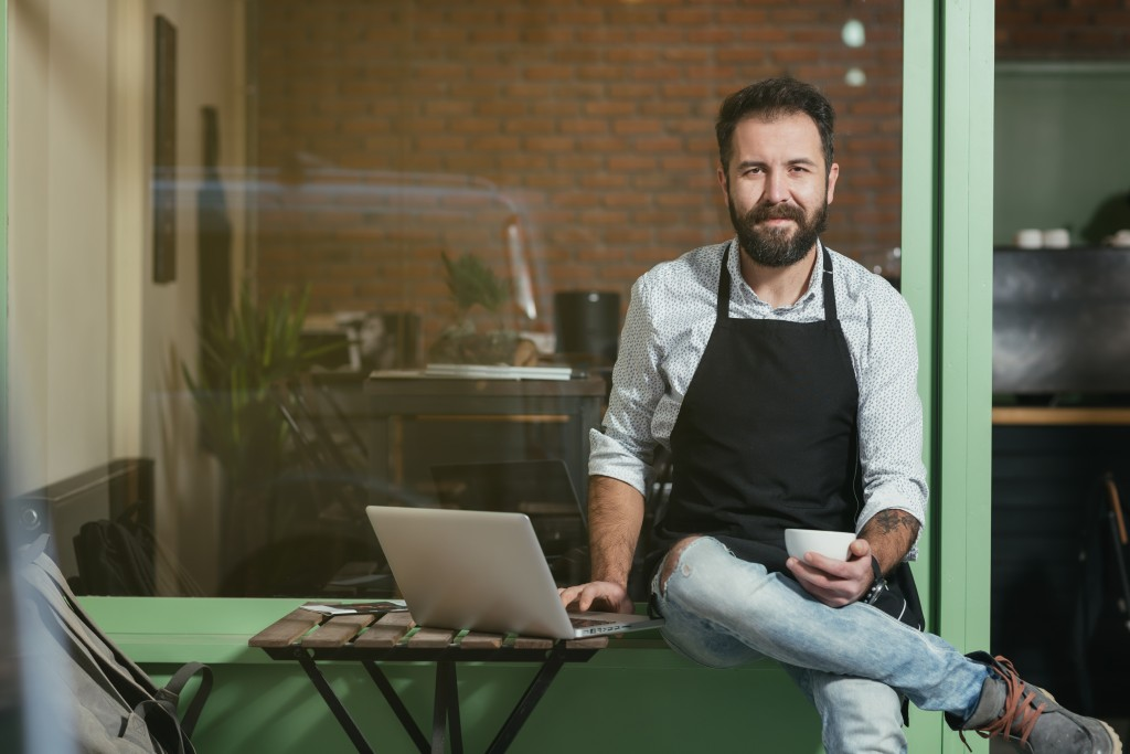 Businessman wearing apron while sitting beside laptop