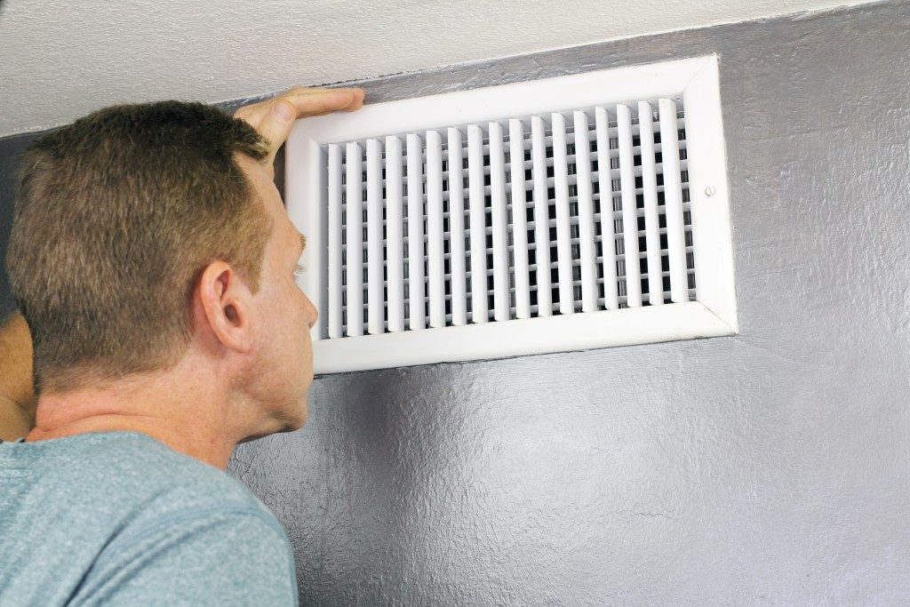 Mature man examining air vent grid