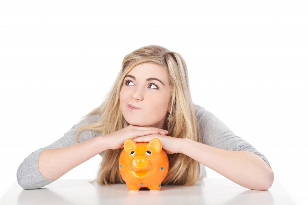 Image of woman posing with piggy bank.