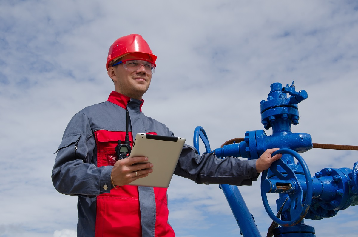 man with clipboard working with pump