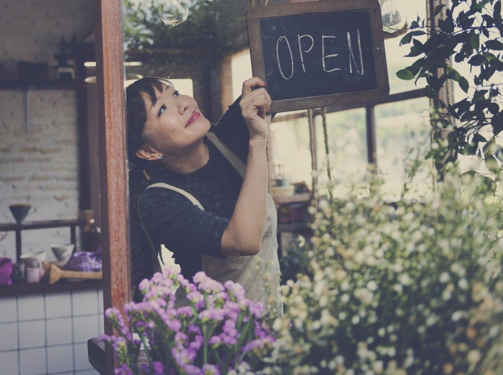 """Female placing """"open"""" sign in front of store"""